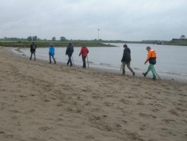 groepje mannen lopen langs de waterkant met stokken in hun hand